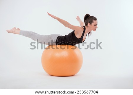 Portrait of healthy young sportswoman doing exercises   lying on  orange exercise  ball on stomach isolated on white background full length