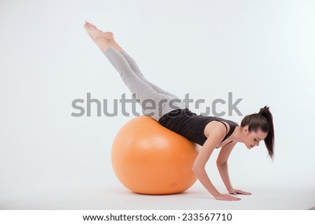 Portrait of healthy young sportswoman doing exercises   lying on  orange exercise  ball on stomach leaning on floor isolated on white background full length