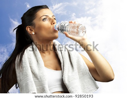portrait of healthy young woman drinking water against a cloudy sky background