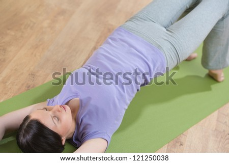 Portrait of healthy young woman practicing yoga exercise on mat at home