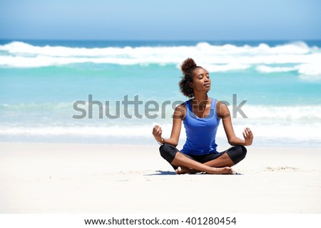 Portrait of healthy young yoga woman sitting in lotus pose at the beach - stock photo