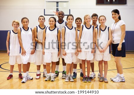 Portrait Of High School Sports Team In Gym With Coach - stock photo