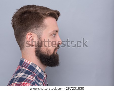 Portrait of hipster bearded man's side face. Man in plaid shirt with short hair on sides posing near grey background. - stock photo