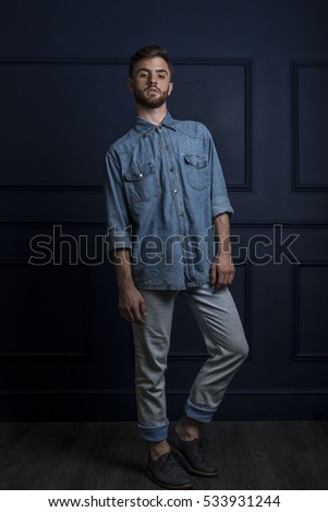 portrait of hipster dressed in blue denim shirt jeans and shoes in studio