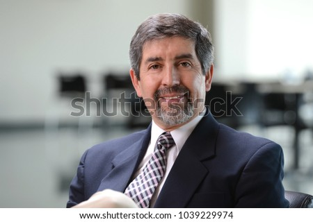 Portrait of Hispanic businessman smiling inside office space