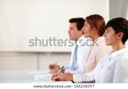 Portrait of hispanic colleagues listening to a conference while smiling on office