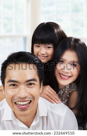 Portrait of Hispanic family smiling on camera at home - stock photo