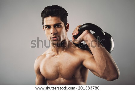 Portrait of hispanic fitness male model holding kettle bell on grey background. Shirtless young doing crossfit work out in studio. - stock photo