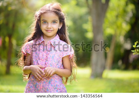 Portrait of hispanic girl with deep blue eyes in sunny park - stock photo