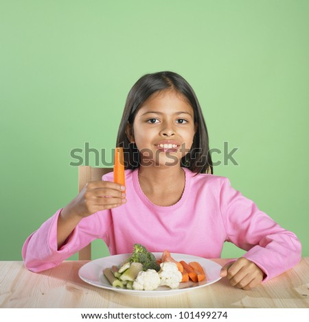 Portrait of Hispanic girl with plate of vegetables