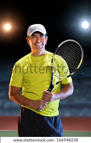 Portrait of Hispanic senior player holding racket  standing on tennis court