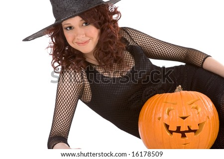 Portrait of Hispanic teenager girl in black Halloween hat and fishnet dress with carved pumpkin (Jack O' Lantern)