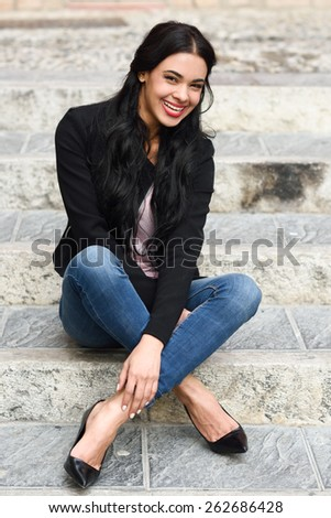 Portrait of hispanic young woman smiling and wearing casual clothes sitting on steps in urban background - stock photo
