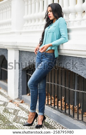 Portrait of hispanic young woman wearing casual clothes in urban background - stock photo