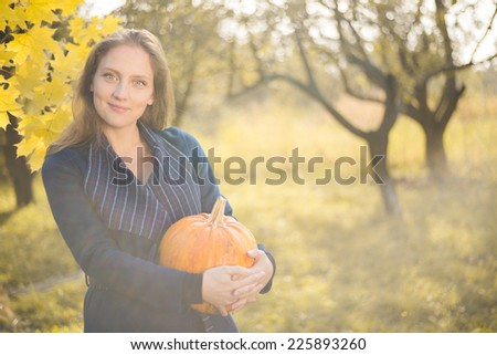 portrait of holding pumpkin elegant beautiful blond young woman having fun happy smiling and looking at camera on autumn copy space outdoors background - stock photo