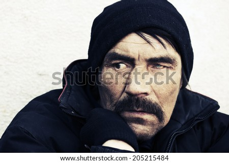 Portrait of homeless man in despair - stock photo