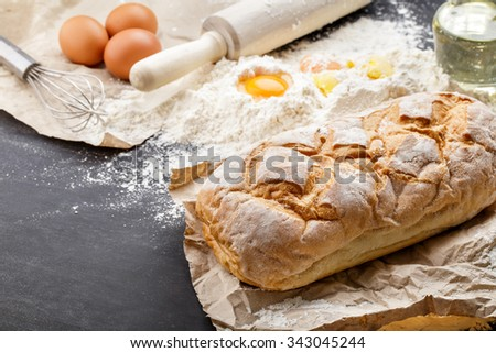 portrait of homemade gluten free bread with ingredients on black board - stock photo