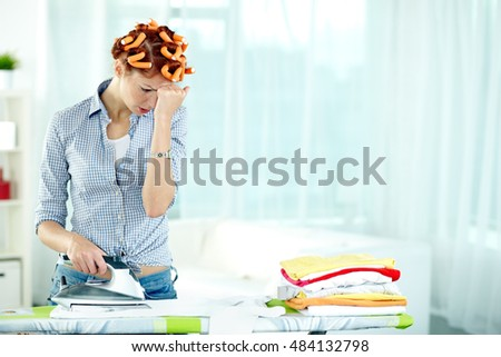 Portrait of housewife with iron having trouble