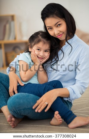 Portrait of hugging Asian mother and daughter  looking at camera
