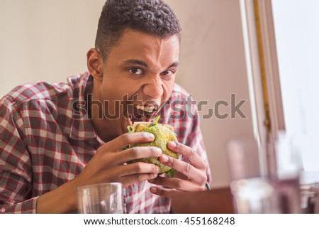 Portrait of hungry man eating vegan burger in vegan restaurant or cafe. Handsome man with short hair looking at camera while sitting at table and having lunch.