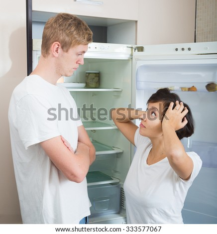 Portrait of hungry young adults near fridge with empty shelves