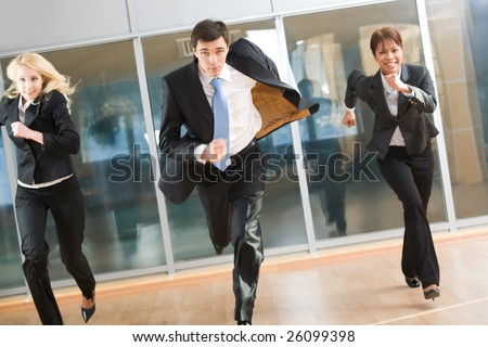 Portrait of hurrying people in suits running forwards for work with optimistic expression - stock photo