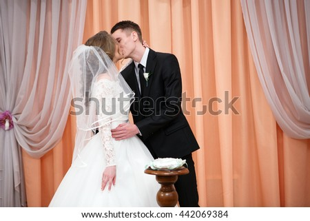 Portrait of husband and wife exchange rings at the registry office - stock photo