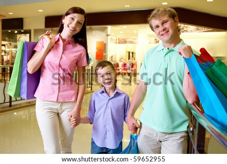 Portrait of husband and wife with their son looking at camera in trade center - stock photo