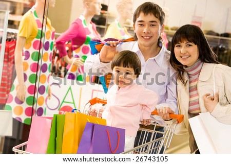 Portrait of husband, wife and their pretty daughter in the trade center - stock photo