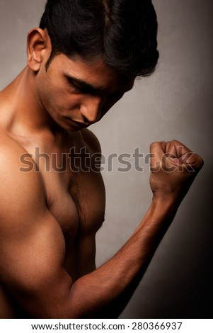 Portrait of Indian angry man over dark background
