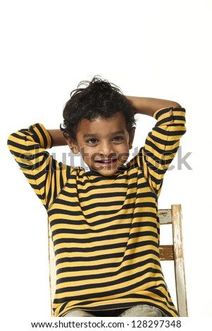 Portrait of Indian boy sitting on chair
