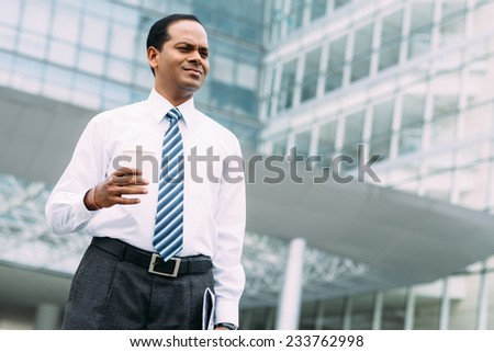 Portrait of Indian businessman with a cup of coffee outdoors - stock photo