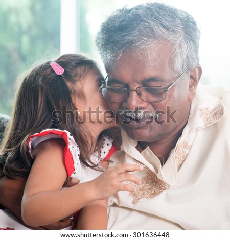 Portrait of Indian family at home. Grandchild kissing grandparent. Grandfather and granddaughter. Asian people living lifestyle. - stock photo