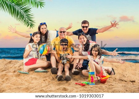 portrait of Indian family enjoying vacation at beach with suitcase, beach ball, clicking selfie picture