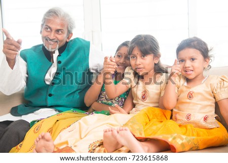 Portrait of Indian family watching movie at home, all finger pointing away. Happy Asian father and children indoors lifestyle.