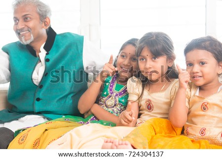 Portrait of Indian family watching tv at home. Happy Asian father and children indoors lifestyle.
