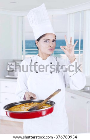 Portrait of indian female chef showing ok sign while holding pan and standing in the kitchen - stock photo