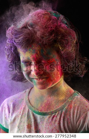Portrait of Indian girl with colored powder thrown on her face in a dark background. Concept for Indian festival Holi. - stock photo