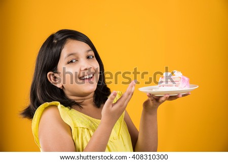 portrait of Indian kid eating cake or pastry, cute little girl eating cake, girl eating strawberry cake over yellow background - stock photo