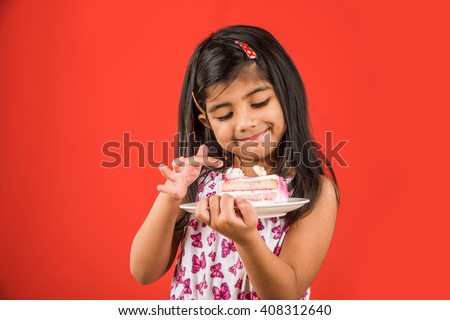 portrait of Indian kid eating cake or pastry, cute little girl eating cake, girl eating strawberry cake over red background - stock photo