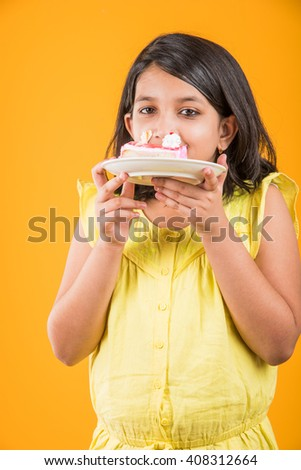 portrait of Indian kid eating cake or pastry, cute little girl eating cake, girl eating strawberry cake or pastry over yellow background - stock photo