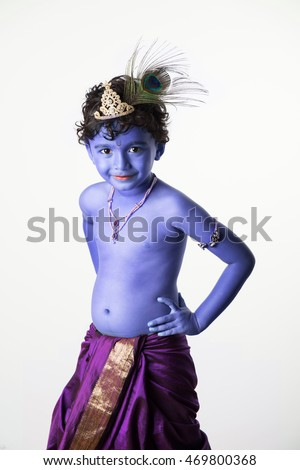 portrait of indian kid posing as bal krishna, having blue skin colour, crown and peacock feather in hair