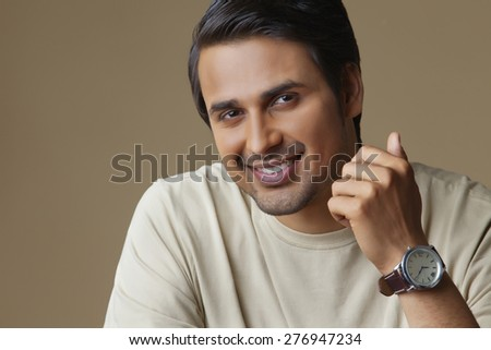 Portrait of Indian man smiling over colored background