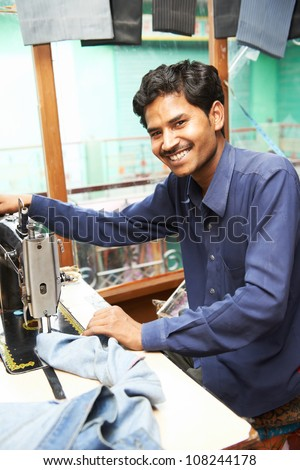 Portrait of indian man tailor at work place with sewing machine - stock photo