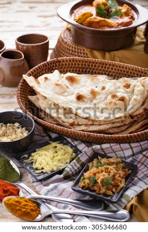 portrait of indian naan bread with chicken curry and some ingredients - stock photo