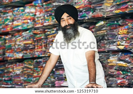 Portrait of Indian sikh man seller in turban with bushy beard at shop - stock photo