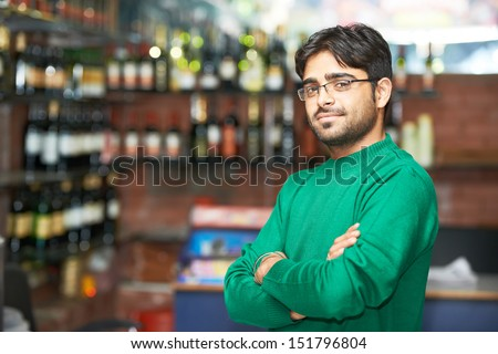 Portrait of Indian sikh man seller with bushy beard at shop - stock photo