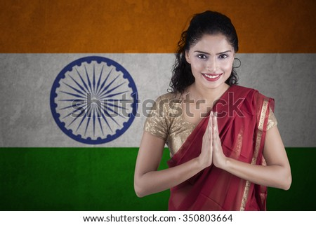 Portrait of indian woman wearing traditional clothes with greeting gesture in front of Indian flag - stock photo