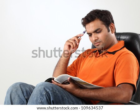 Portrait of indian young man reading a book