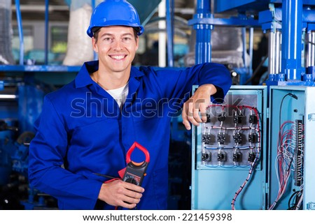 portrait of industrial electrician with insulation tester in factory - stock photo